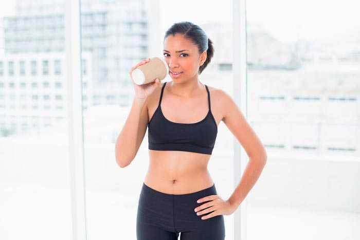 девушка пьет кофе на тренировке